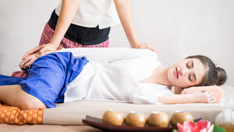 girl-blue-plants-laying-down-mat-thai-massage.jpg
