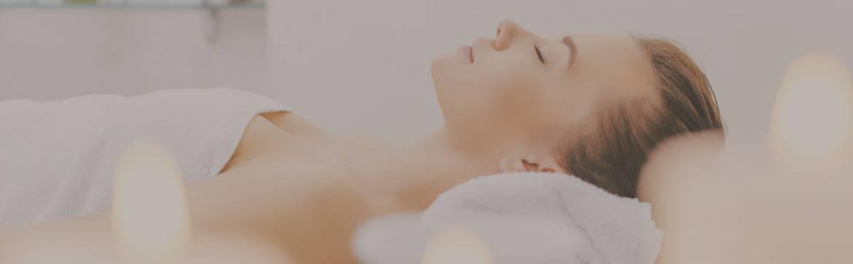 darker-layer-woman-facing-up-white-towel-candles-closeup.jpg